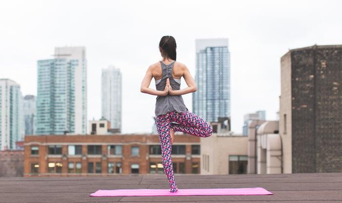 woman-standing-on-pink-yoga-mat-meditating-373946-1